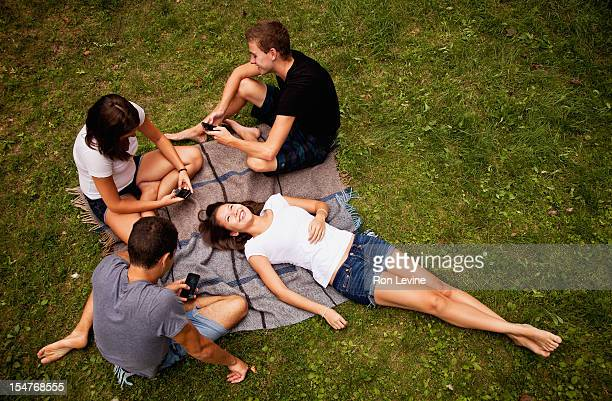 Group of teens using cellphones outside