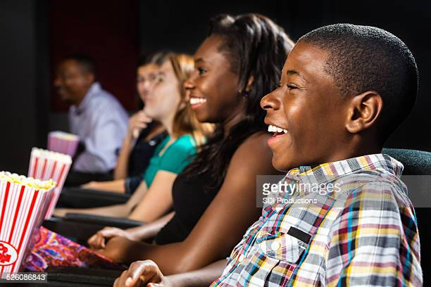Group of teens watching film together in local movie theater