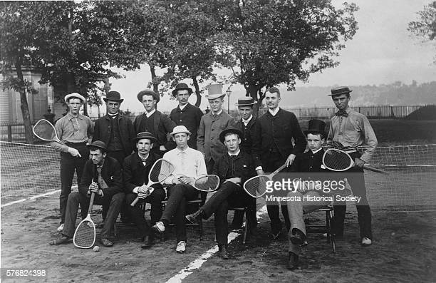 A group of tennis players pose by the net of a clay court Standing in back row Wm Armstrong Whitney Wall unknown unknown Will Farnum Alec Horn...