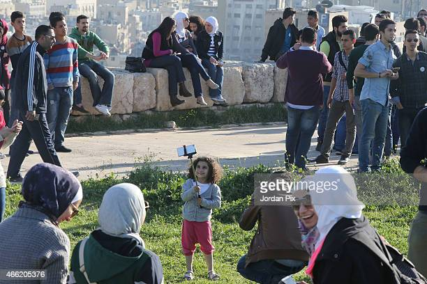 A group of tens of Jordanians take a selfie with a smartphone in the Citadel site in the center of Amman Jordan on March 14 2015 Jordanian youth...