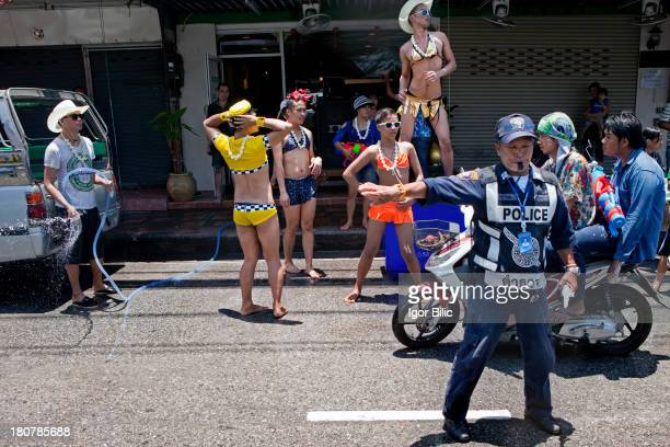 Group of Thai gay men, dance on the street in front of a massage parlor where they work, during the Songkran water festival in Pattaya city,...