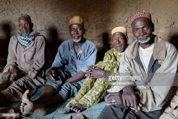 Group of the elders of Yaka inside the hut where the keep the knifes for the circumcision ceremony They are the ones in charge of organising the...
