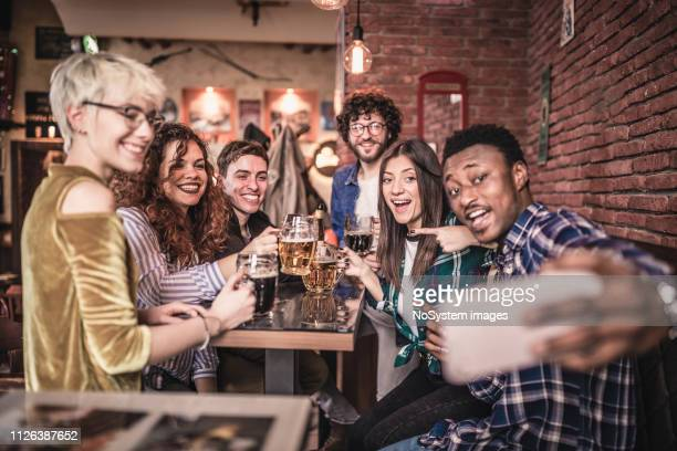 group of the friends having fun in the pub, taking selfie - generation z stock pictures, royalty-free photos & images