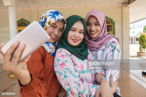 group of three asian muslim girls taking selfie with smile - indonesian culture stock pictures, royalty-free photos & images