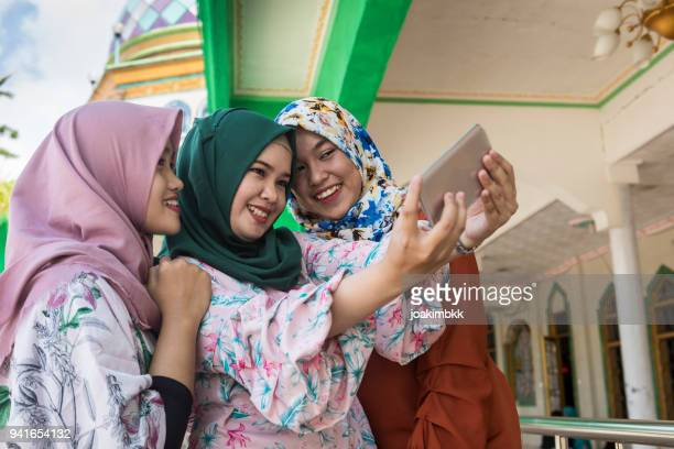 Group of three Asian Muslim girls taking selfie with smile