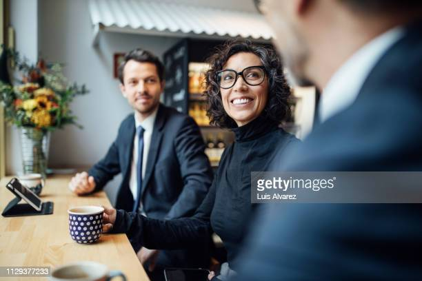 group of three business people sitting at a coffee shop - three people stock pictures, royalty-free photos & images