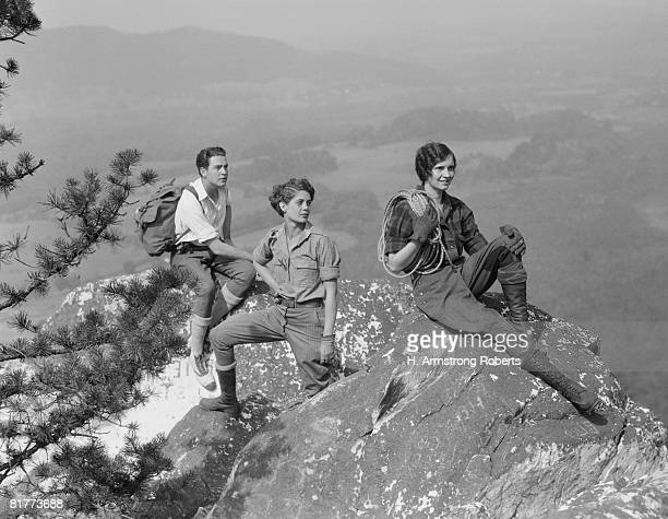 Group of three climbers atop mountain.