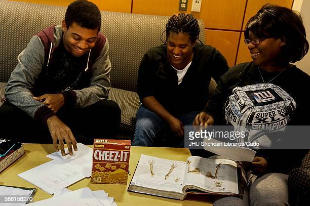 A group of three college students laughing and smiling studies together in the Milton S Eisenhower Library on the Homewood campus of the Johns...