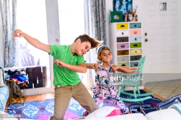 group of three elementary age siblings have a dance party in the living room at home with energy - anti quarantine stock pictures, royalty-free photos & images