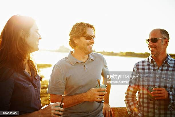 Group of three friends in discussion on dock