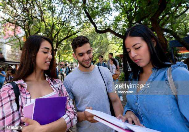 group of three friends studying together while standing at campus reading their notes of a previous class on notebook - hispanolistic stock photos and pictures