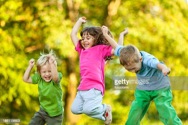 Group of three happy children jumping outdoors