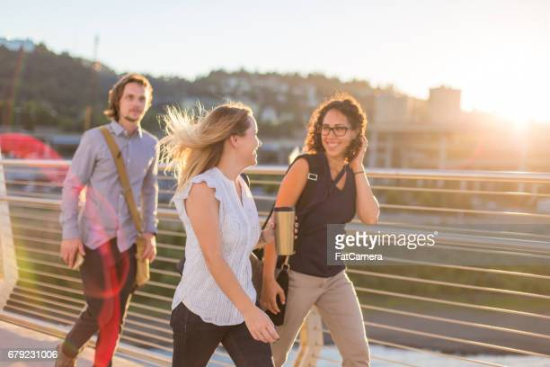 Group of three happy friends walking along bridge on sunny day