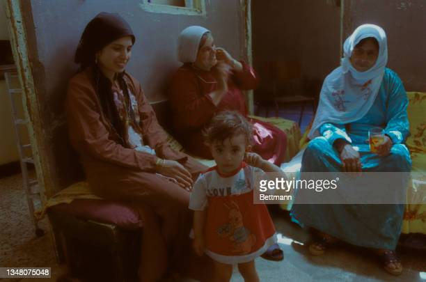 Group of three Middle Eastern women, two wearing headscarves and the other in a hijab, sitting around with a small child standing before them in an...