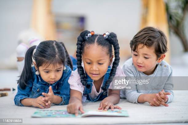 a group of three multi-ethnic children lay on the floor reading together stock photo - preschool student stock pictures, royalty-free photos & images