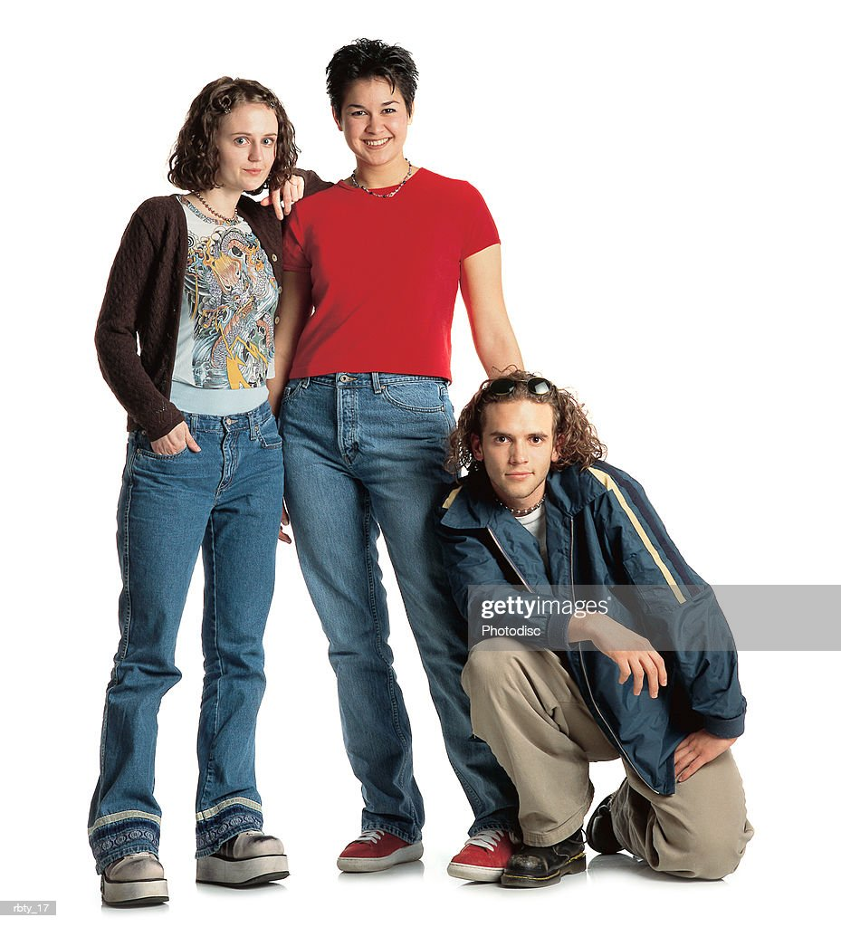group of three teenage friends wearing alternative clothes with two girls  standing and a boy kneeling down : Foto de stock