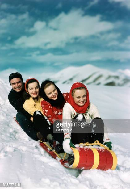 Group of three women one man on red and yellow toboggan sledding in the winter snow Los Angeles California 1949