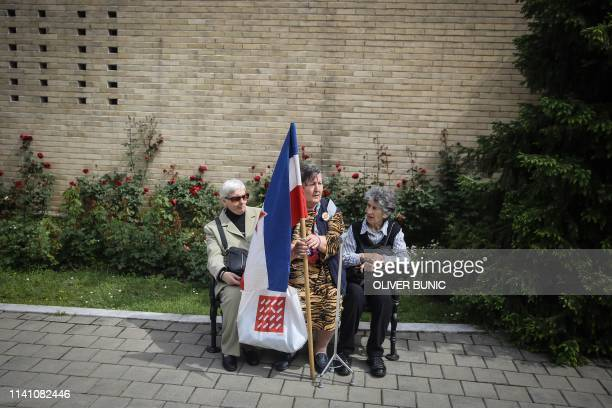 A group of three women sit on a bench as they hold a Yugoslavian flag upon their arrival to take part in a rally at the grave of late Yugoslavia's...