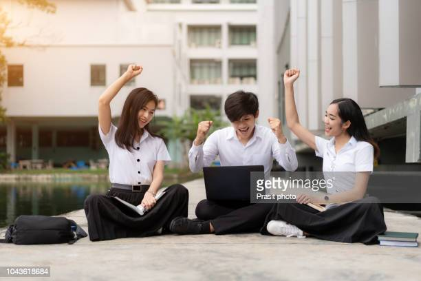 group of three young asian students watching exam results in a laptop in university campus. - stipendium stock-fotos und bilder