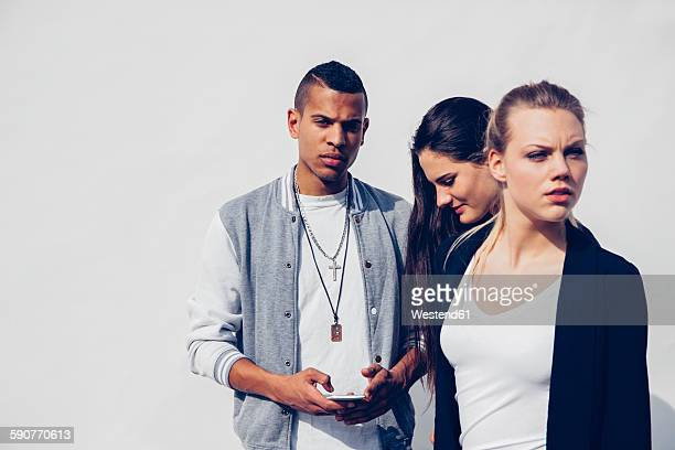 Group of three young people in front of white background