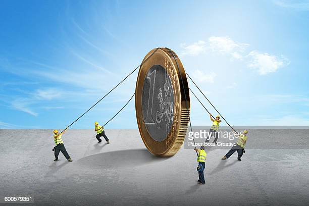 group of tiny men carrying one giant euro coin - 1 euro photos et images de collection