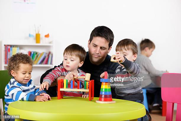 Group Of Toddlers Being Supervised Playing With Multi-coloured Wooden Toys