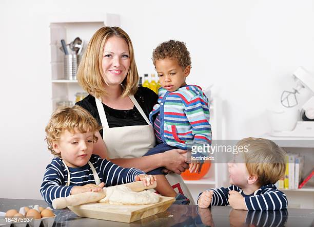 Group Of Toddlers Enjoying Home Baking With Carer/ Childminder