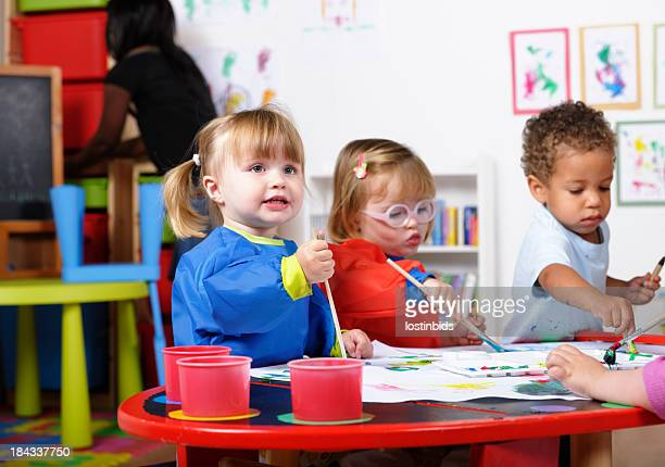 group of toddlers painting while their carer tidies - 2 3 years photos stock photos and pictures
