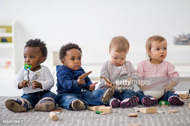 group of toddlers playing together - vier personen stockfoto's en -beelden