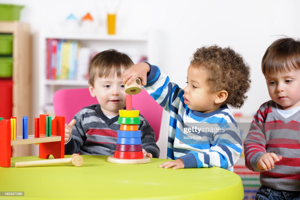 Group Of Toddlers Playing With Multi-coloured Wooden Toys : Stock Photo