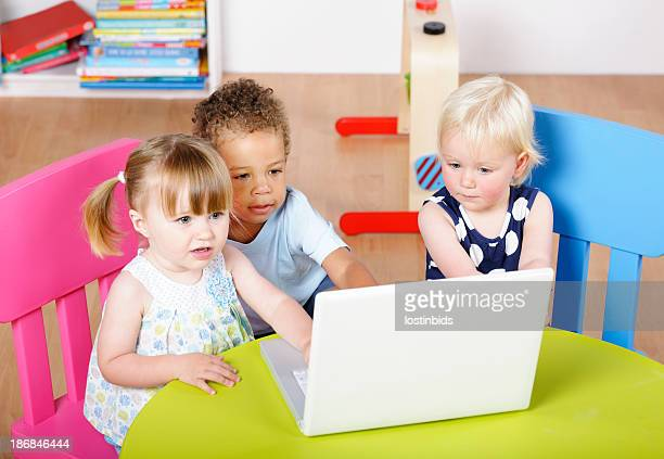 Group Of Toddlers Using  Technology In A Nursery Setting