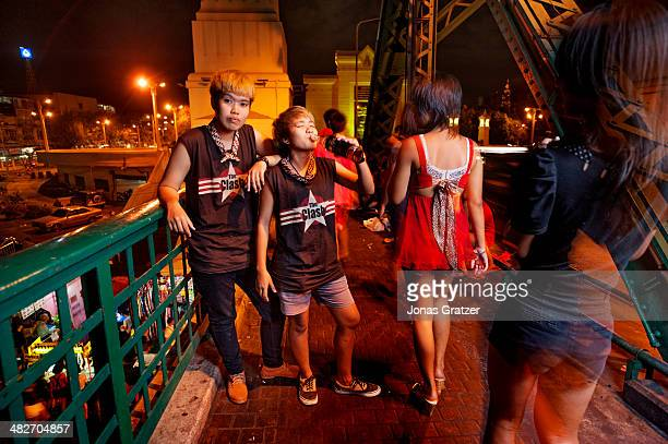 A group of tomboys enjoy a few drinks on their picnic on a bridge over a river in Bangkok city whilst two ladies walk past Tomboys often seek to fit...