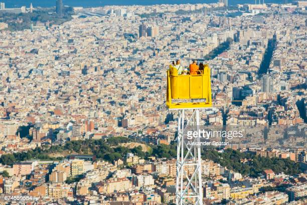 Group of tourists admiring Barcelona from above and taking pictures with their smartphones