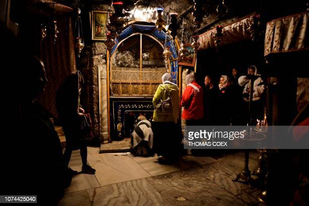 A group of tourists and pilgrims visit the Grotto believed to be the exact spot where Jesus Christ was born as others pray at the Church of the...
