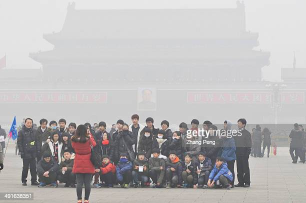 A group of tourists are taking souvenir photos in Tienanmen Square behind them the picture of Chairman Mao is nearly invisible in the hazy air