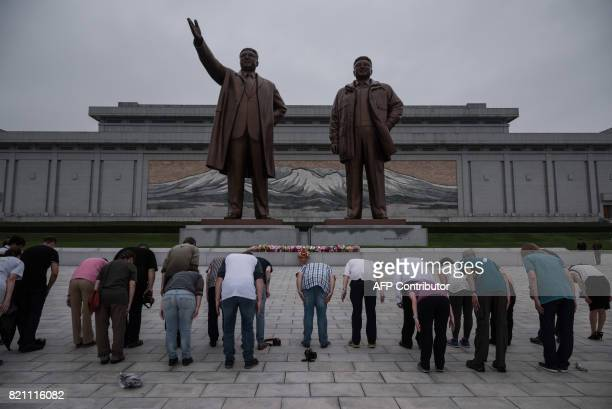 A group of tourists bow before statues of late North Korean leaders Kim IlSung and Kim JongIl on Mansu hill in Pyongyang on July 23 2017 The...