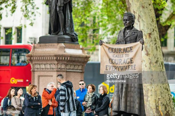 group of tourists gather by the newly erected statue of millicent fawcett in parliament square, london, uk, she campaigned for women's right to vote during the early 20th century and is seen as one of the most influential feminists of the past 100 years. - suffragette stock pictures, royalty-free photos & images