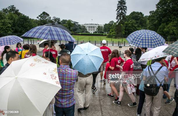 A group of tourists gather in the rain at the south lawn to take pictures of the White House on June 5 2017 in Washington DC The nation's capital the...