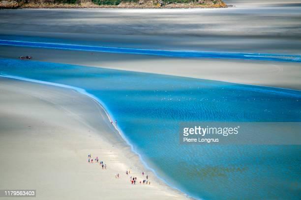 group of tourists hiking along flowing sea water in the bay of mont saint-michel - haute normandie stockfoto's en -beelden