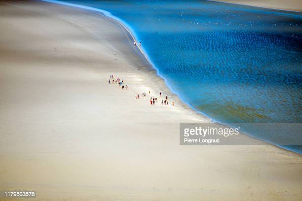 group of tourists hiking along flowing sea water in the bay of mont saint-michel - cotentin photos et images de collection