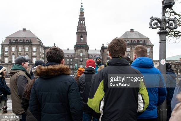group of tourists listening to their guide in front of christiansborg palace on a grey winter day - dorte fjalland stock pictures, royalty-free photos & images