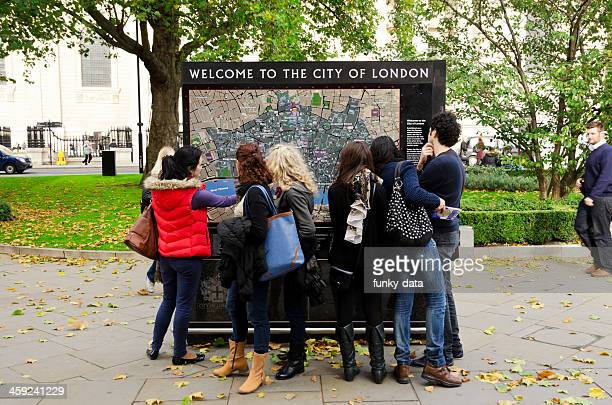 Group of tourists looking at London map
