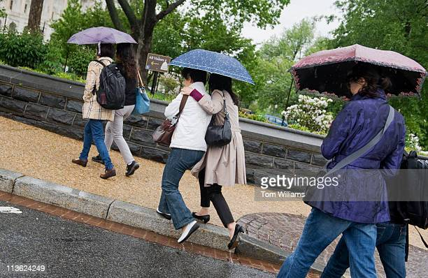 Group of tourists make their way onto the senate side of the Capitol grounds on a rainy Tuesday morning.
