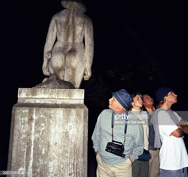 group of tourists, mature man looking at rear of statue, night - close to stock pictures, royalty-free photos & images