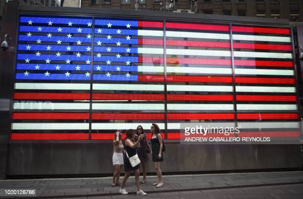 A group of tourists pose for a photo in front of a US National Flag displayed in Times Square in New York on August 20 2018