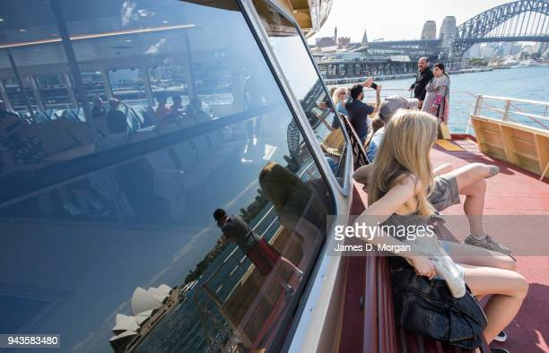A group of tourists sit on a harbour ferry to see the city with the Opera House reflected in one of the windows on April 9 2018 in Sydney Australia...