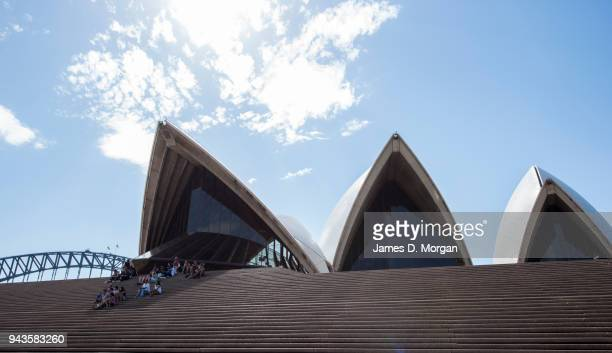 A group of tourists sit under the sails for shade in the afternoon heat beside the Opera House on April 9 2018 in Sydney Australia Sydney has been...