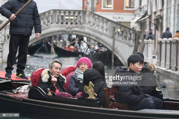 A group of tourists sits on a gondola sailing on a canal of Venice on January 19 2018 / AFP PHOTO / Andrea PATTARO