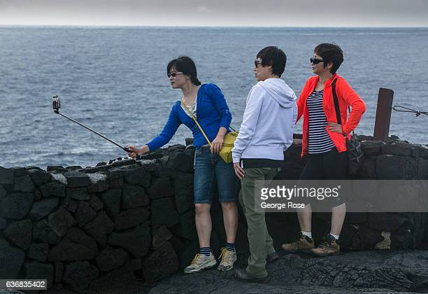 Group of tourists take a selfie near the Naulu Sea Arches on December 12 at Volcanoes National Park, Hawaii. Hawaii, the largest of all the Hawaiian...