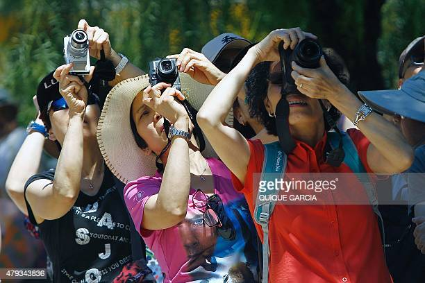 A group of tourists take pictures next to the Spanish architect Gaudi's Sagrada Familia basilica in Barcelona on June 28 2015 Tourists generated 14%...